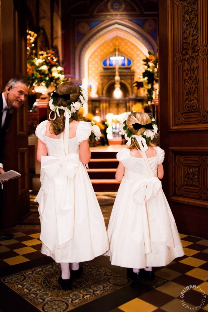 Two flower girls entering wedding venue