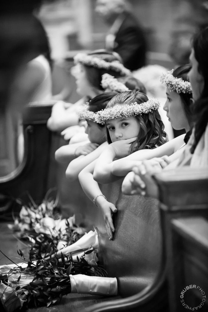 Flower girl peaking at the photographer