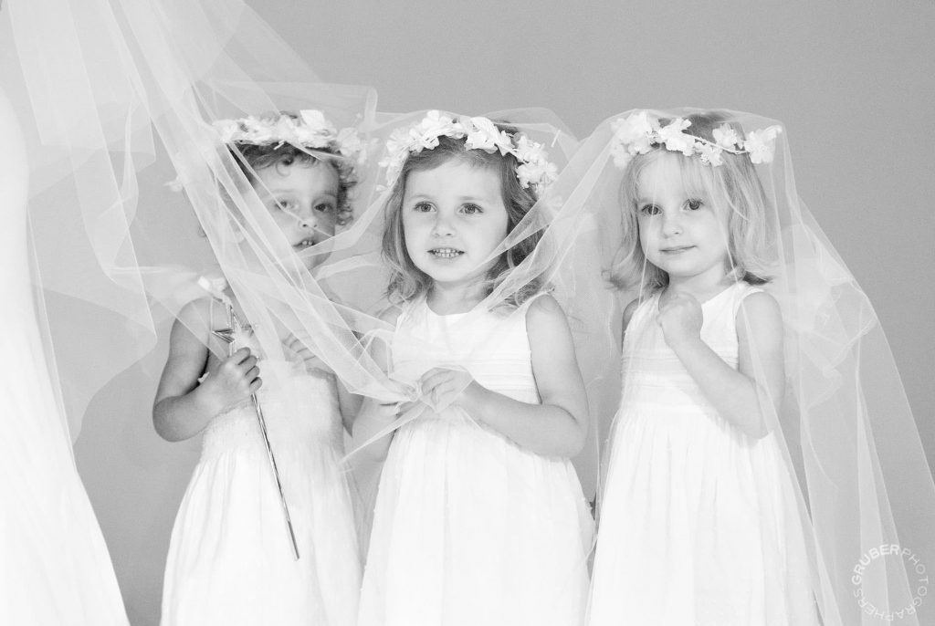 Flower girls under bride's vail