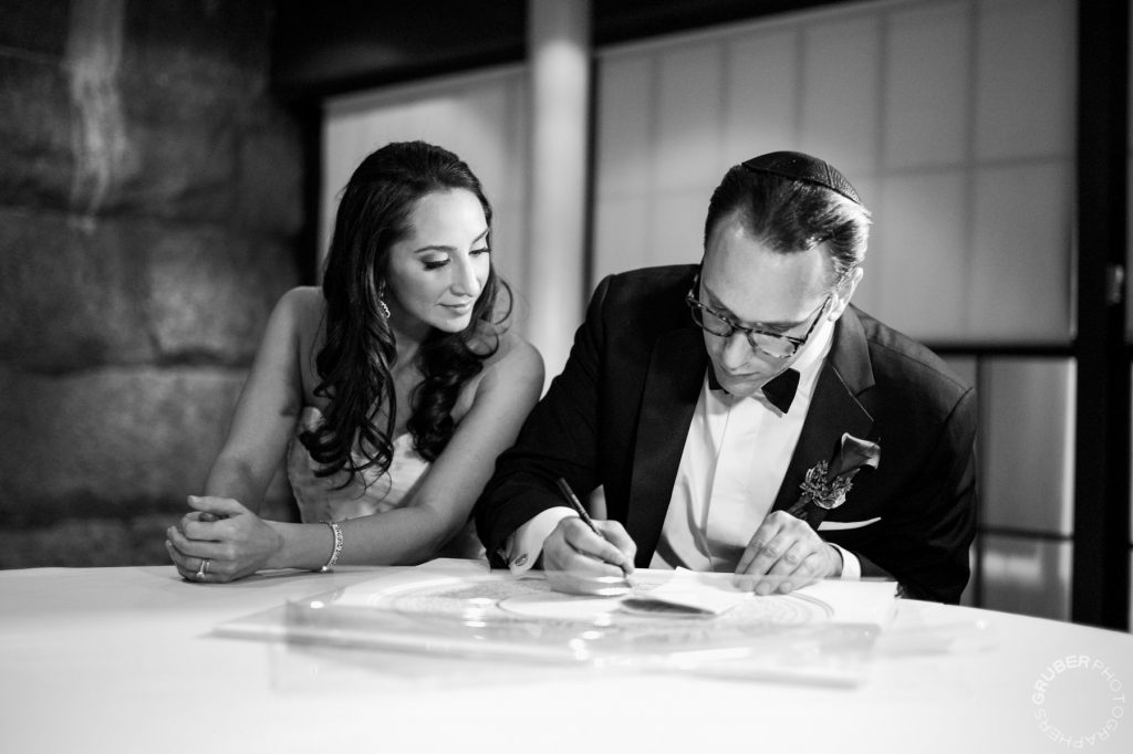 Bride and Groom signing their Ketubah at NYC Luxury Wedding