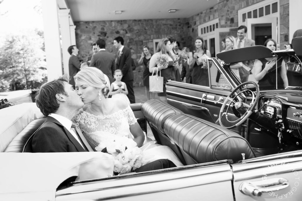 Bride and Groom Kiss in back of Convertible